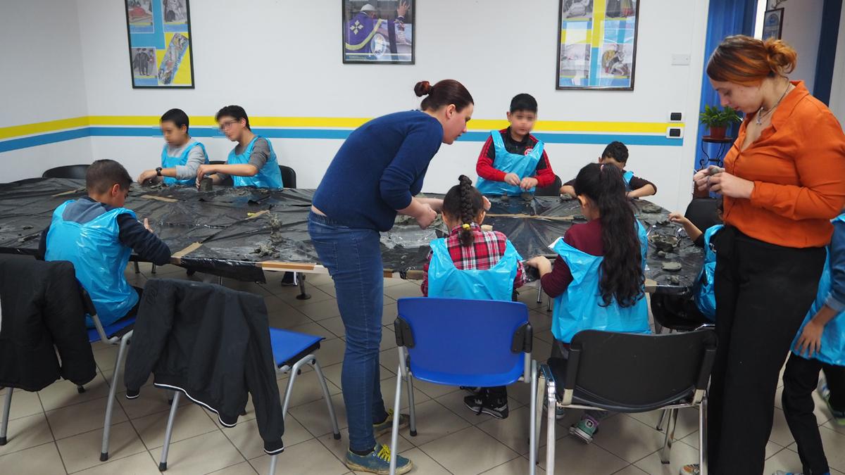 bambini e istruttori a lavoro intorno al tavolo